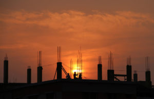 Construction Site at Sunset with Workers Silhouetted